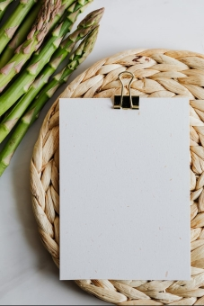 asparagus and blank paper on a mat